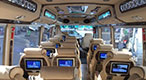 Interior picture of Vehicle Type 1033: 18 seater limousine buses with comfortable reclining seats, personal TV screens, USB charger ports and free wifi.